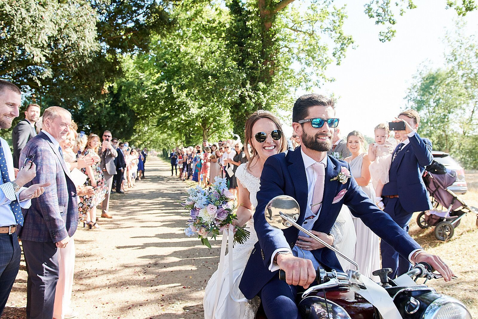 bride and groom on motorbike after their wedding in Norwich by Norfolk Wedding Photographer Faye Amare