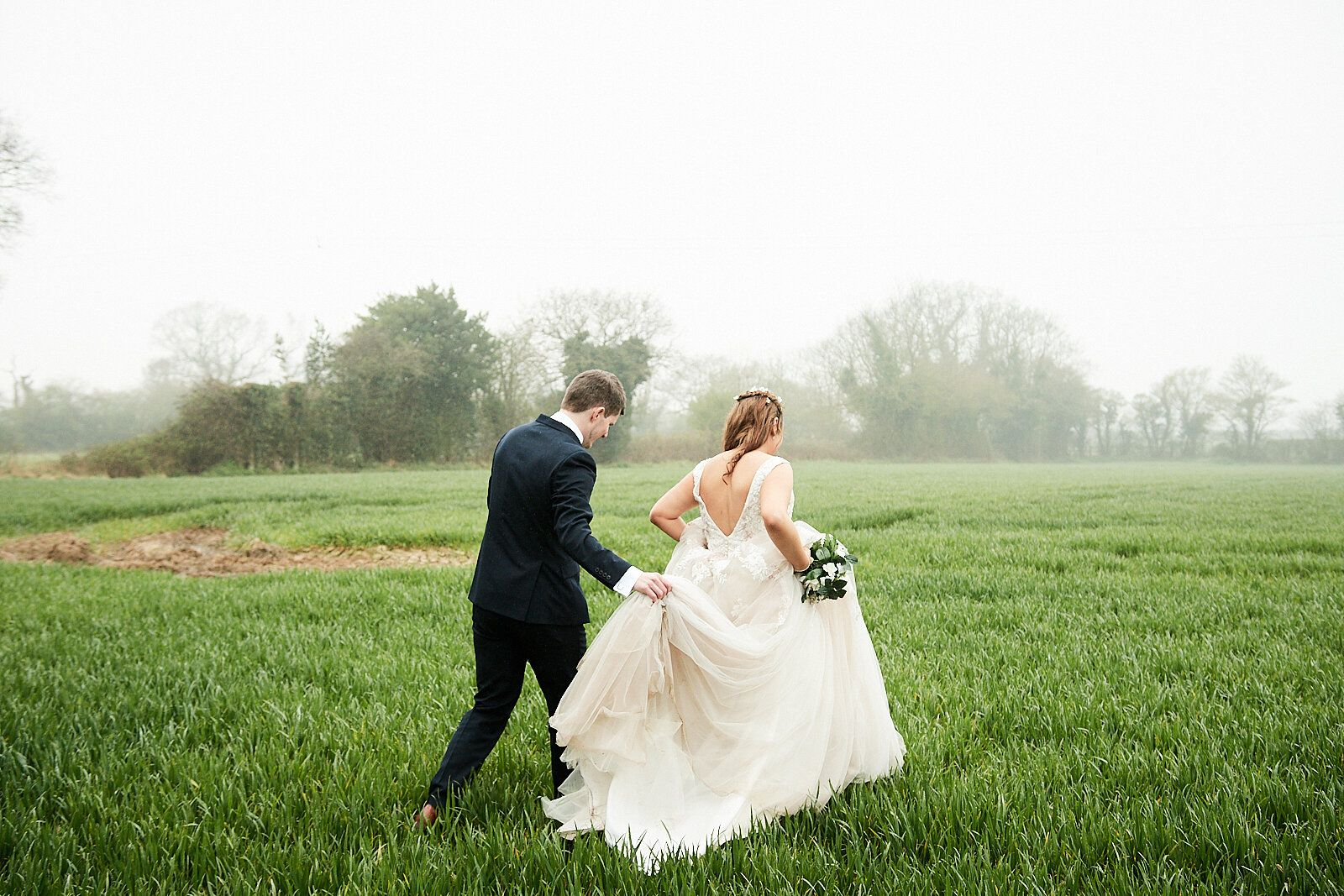 bride and groom walk through misty green field at The Reading Rooms, Norfolk by Norfolk Wedding Photographer Faye Amare