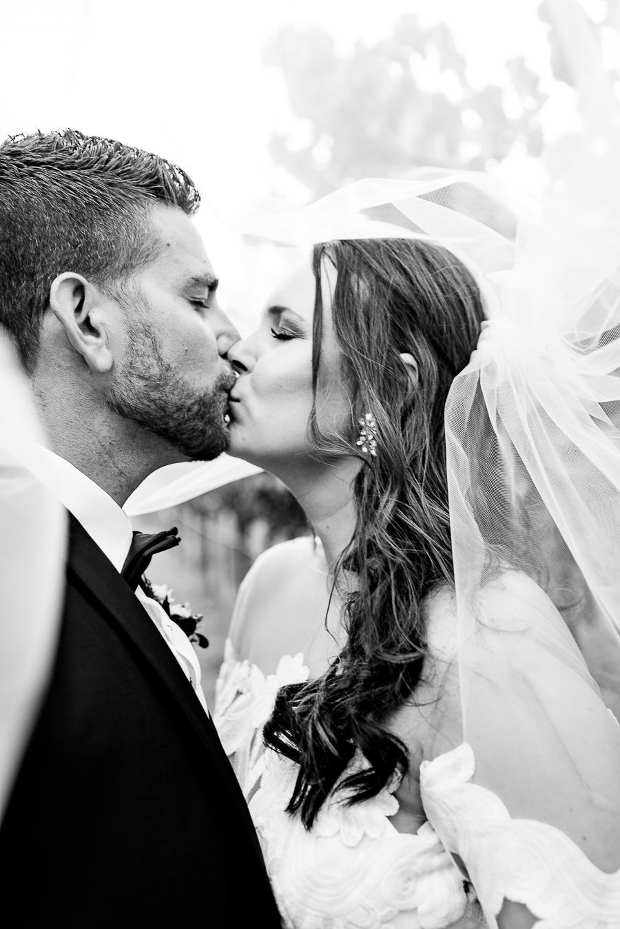 Bride and groom kiss under veil at Pennyroyal Farm wedding in Northern California