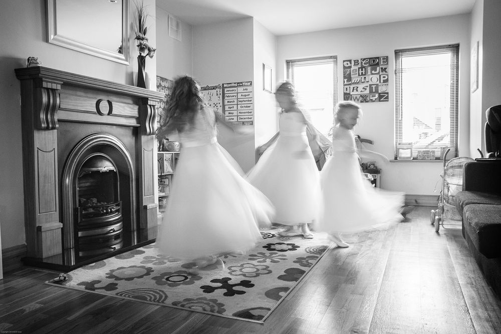 three young bridesmaids spinning round in a blur in brides front room