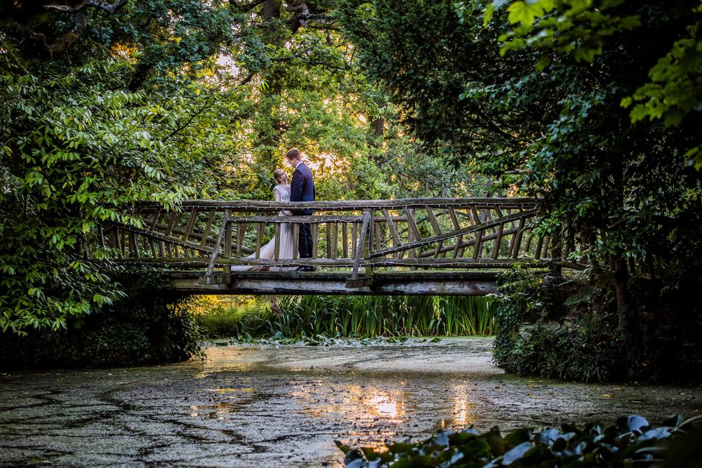 bride and groom on a smallm wooden bridge over the lake at manor bt the lake