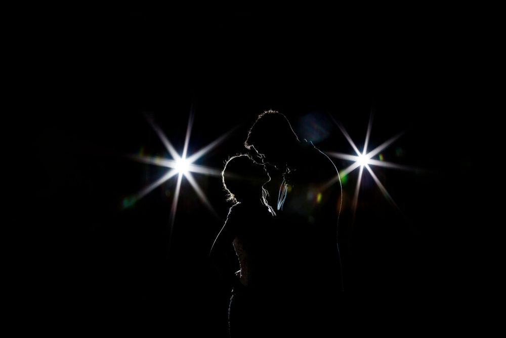 bride and groom together with spot lights from behind at manor by the lake cheltenham