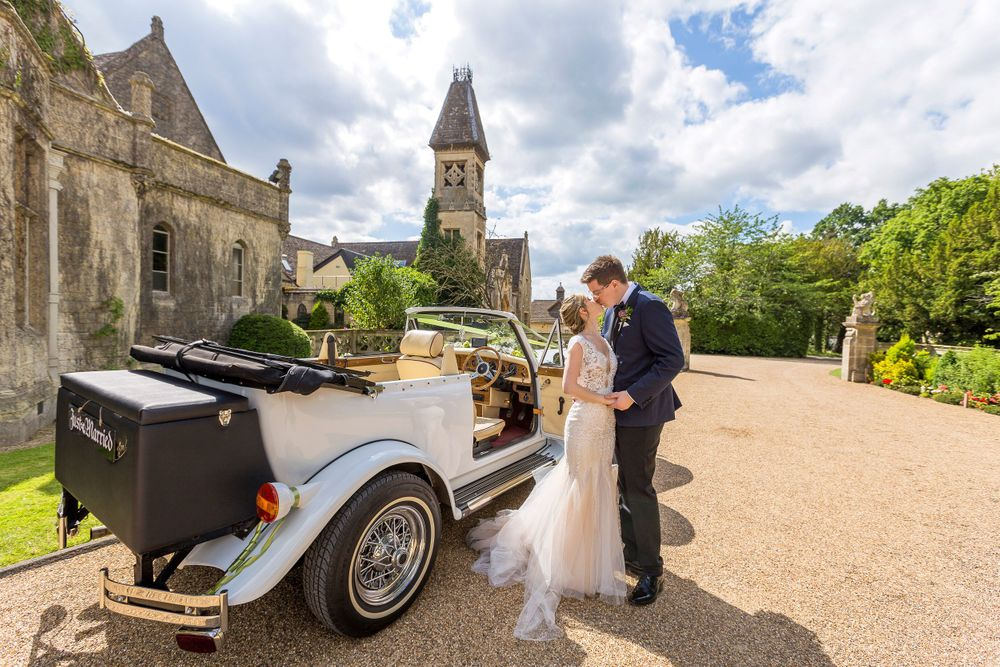 bride and groom with car staring into each other eyes at manor by the lake