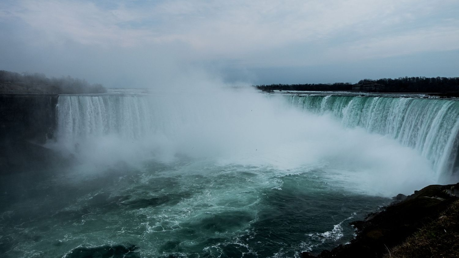 A massive horseshoe shaped water fall on an overcast day, full of mist