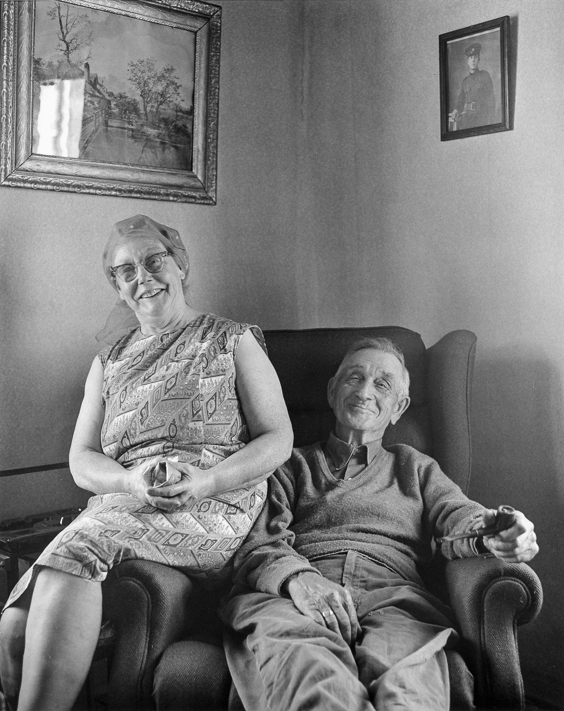 Andrew Ellsworth sitting in his favorite chair with his wife posing on the arm, Rocky Harbour, NFLD