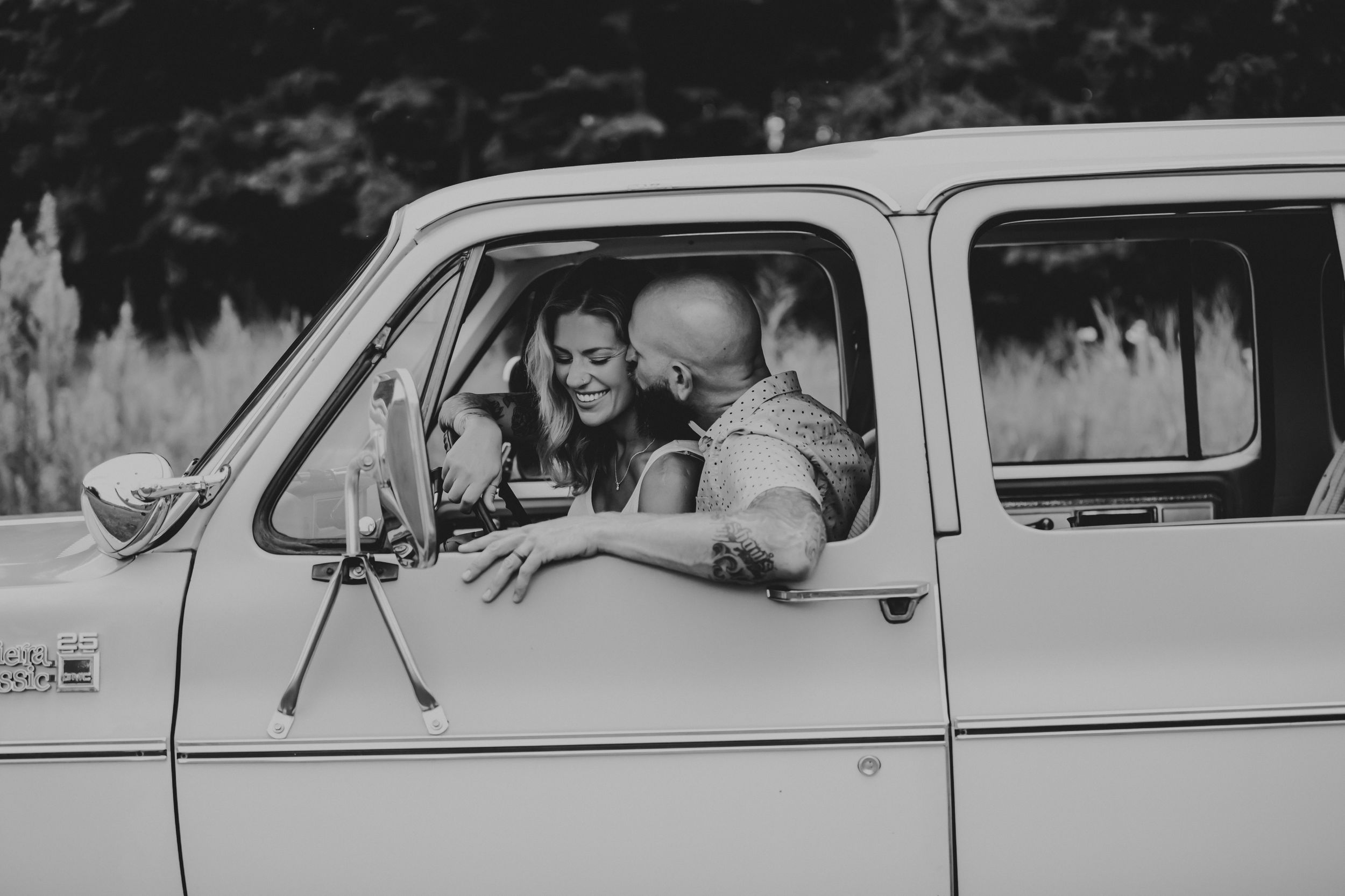 Black and white photo of husband kissing wife's cheek while they sit in the station wagon.