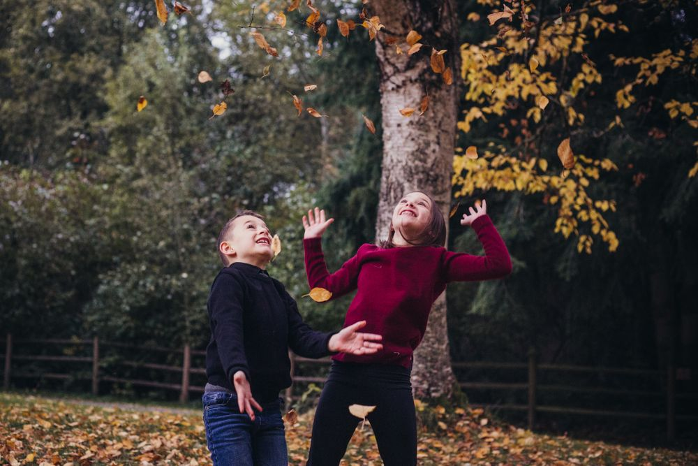 brother and sister throwing fall leaves in the air