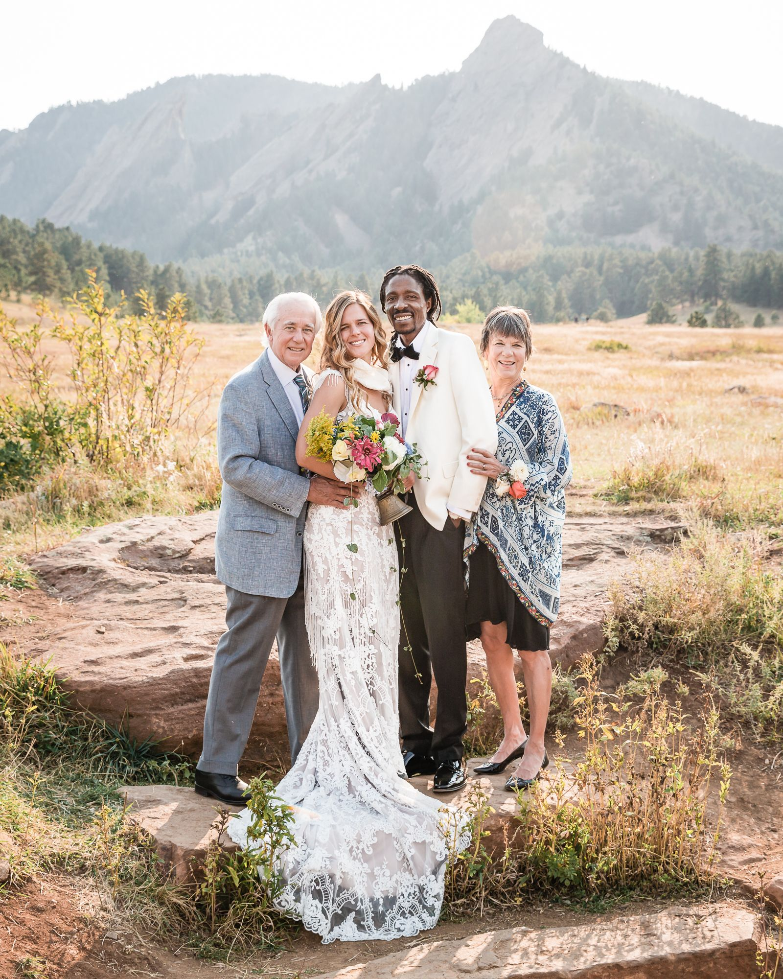 Wedding couple with parents standing in front of the flatirons in Chautauqua Park, Boulder Colorado.
