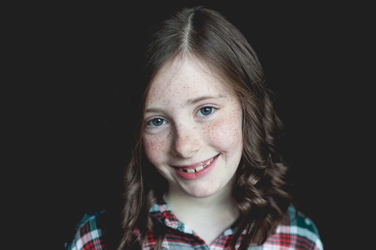 modern school portrait with black backdrop and girl smiling wearing a plaid shirt