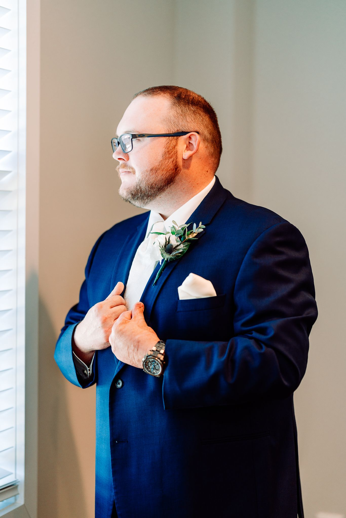 Groom looking at the window at The Blessed Barn in Aynor, SC, by PHV Photo