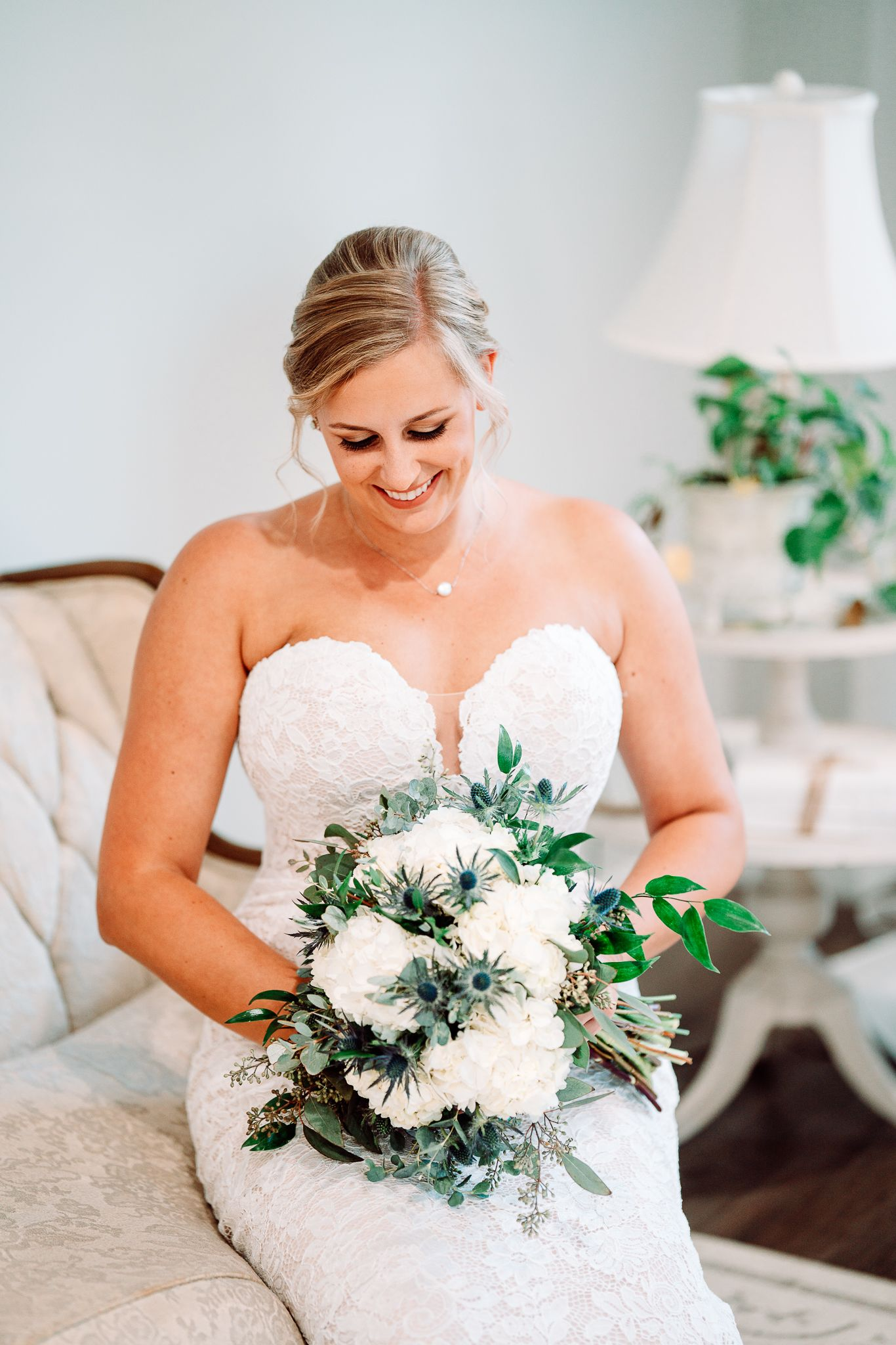 Bride sitting and looking at her bouquet at The Blessed Barn in Aynor, SC, by PHV Photo