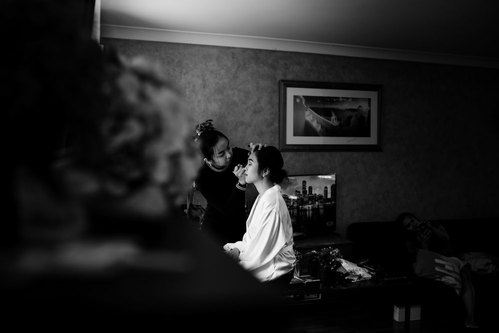 bride getting make up done in her house