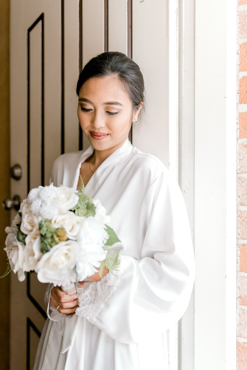 bride getting ready and holding flower bouquet with both hands