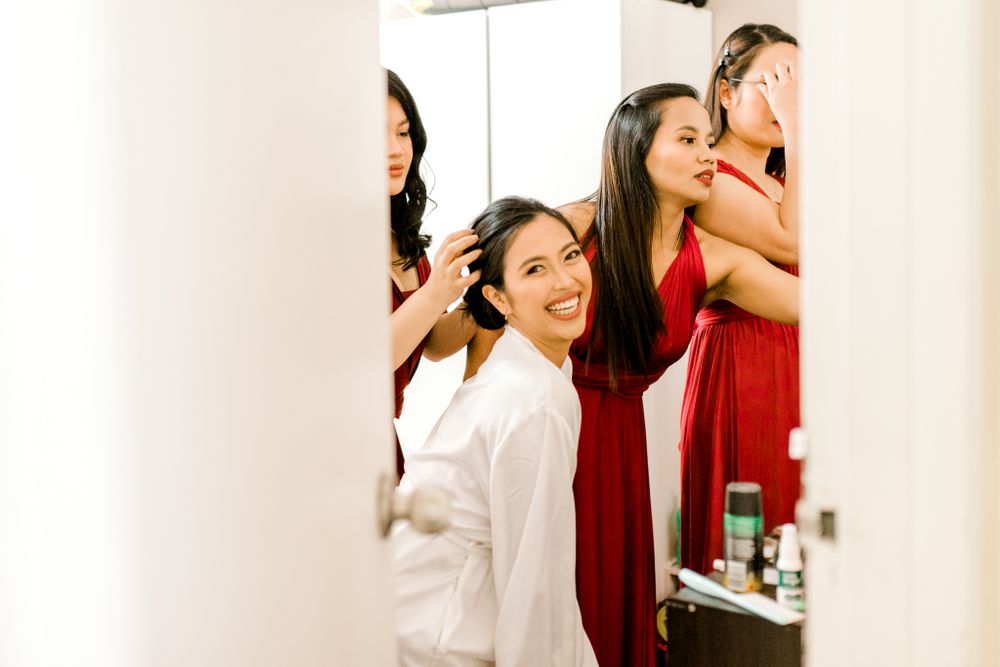 bride surrounded by bridesmaids getting ready