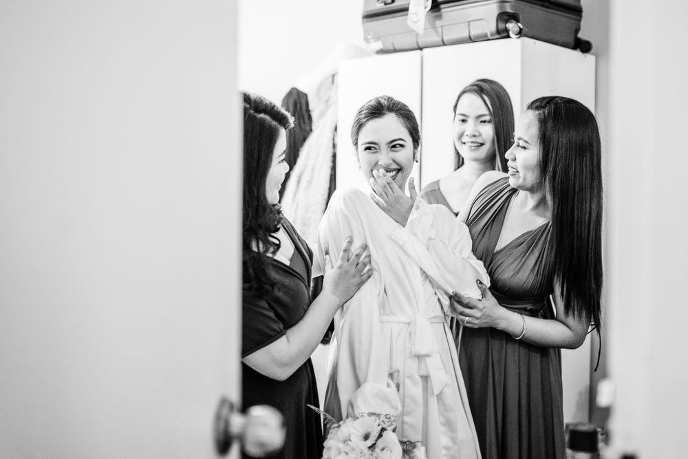 bride in robe having a good time with bridesmaids