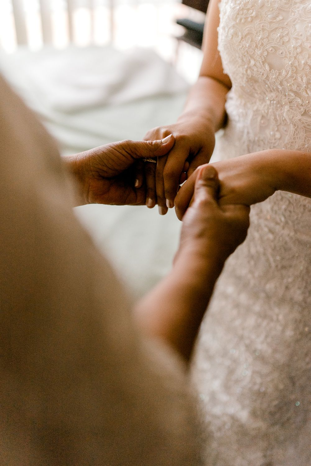 bride and mother holding hands