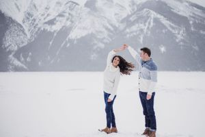 Man twirls fiance in front of Banff mountains in the snow