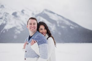 Newly engaged couple hug in Banff in the snow