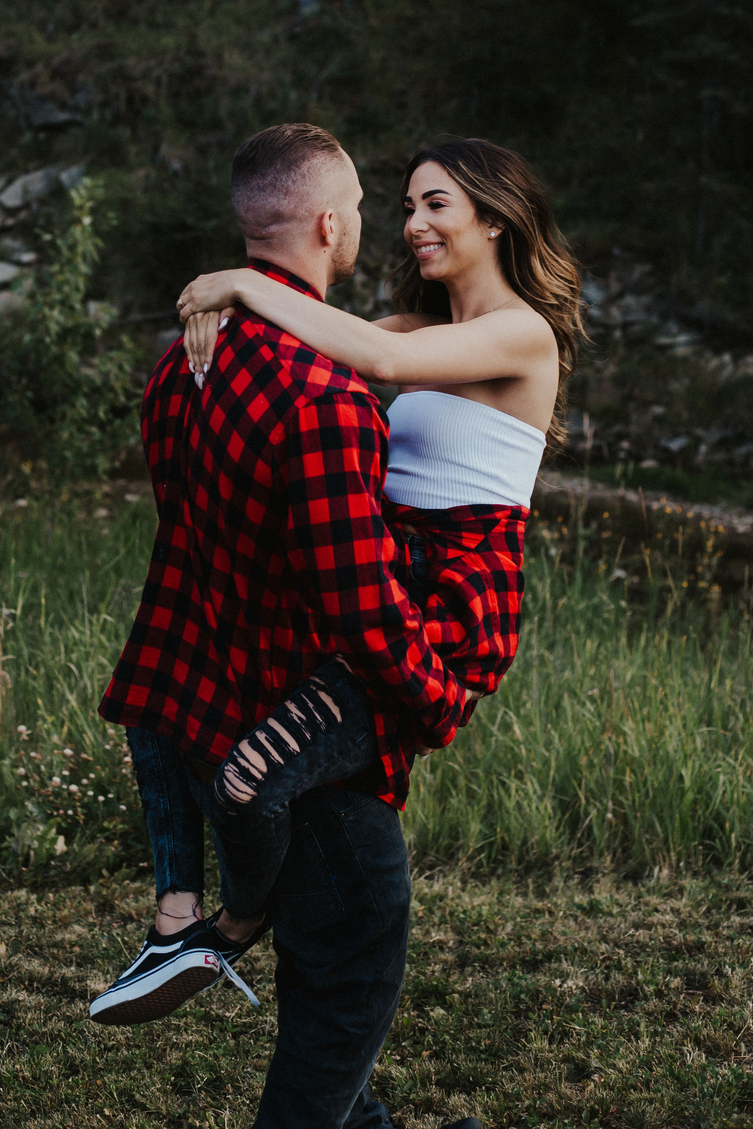 Couple in plaid twirl in the grass