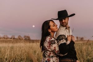 Couple in a field with harvest moon behind at sunset
