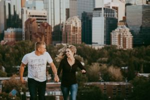Couple holding hands run towards the camera with city skyline view behind them.