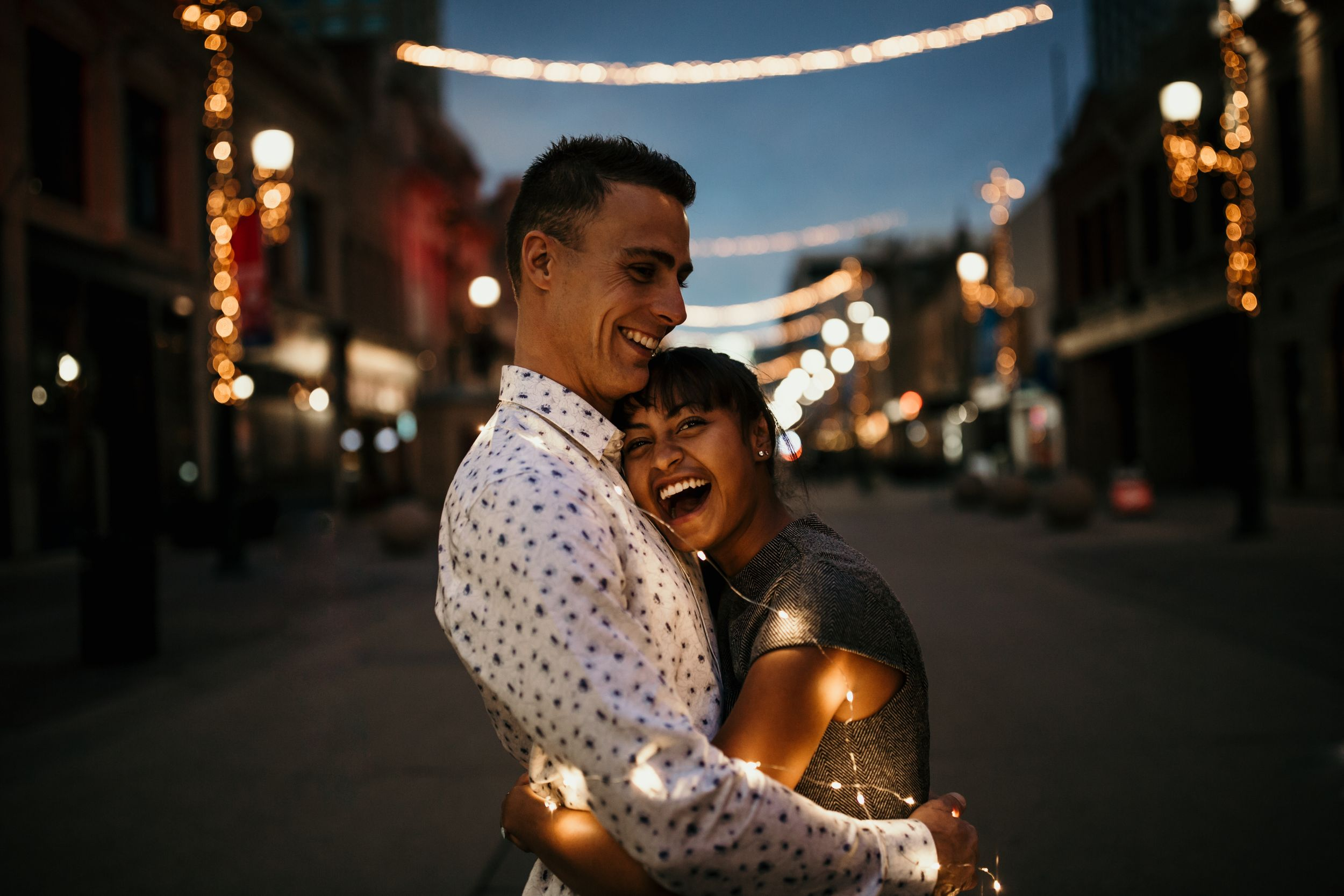 Couple embrace while laughing in front of twinkle lit street