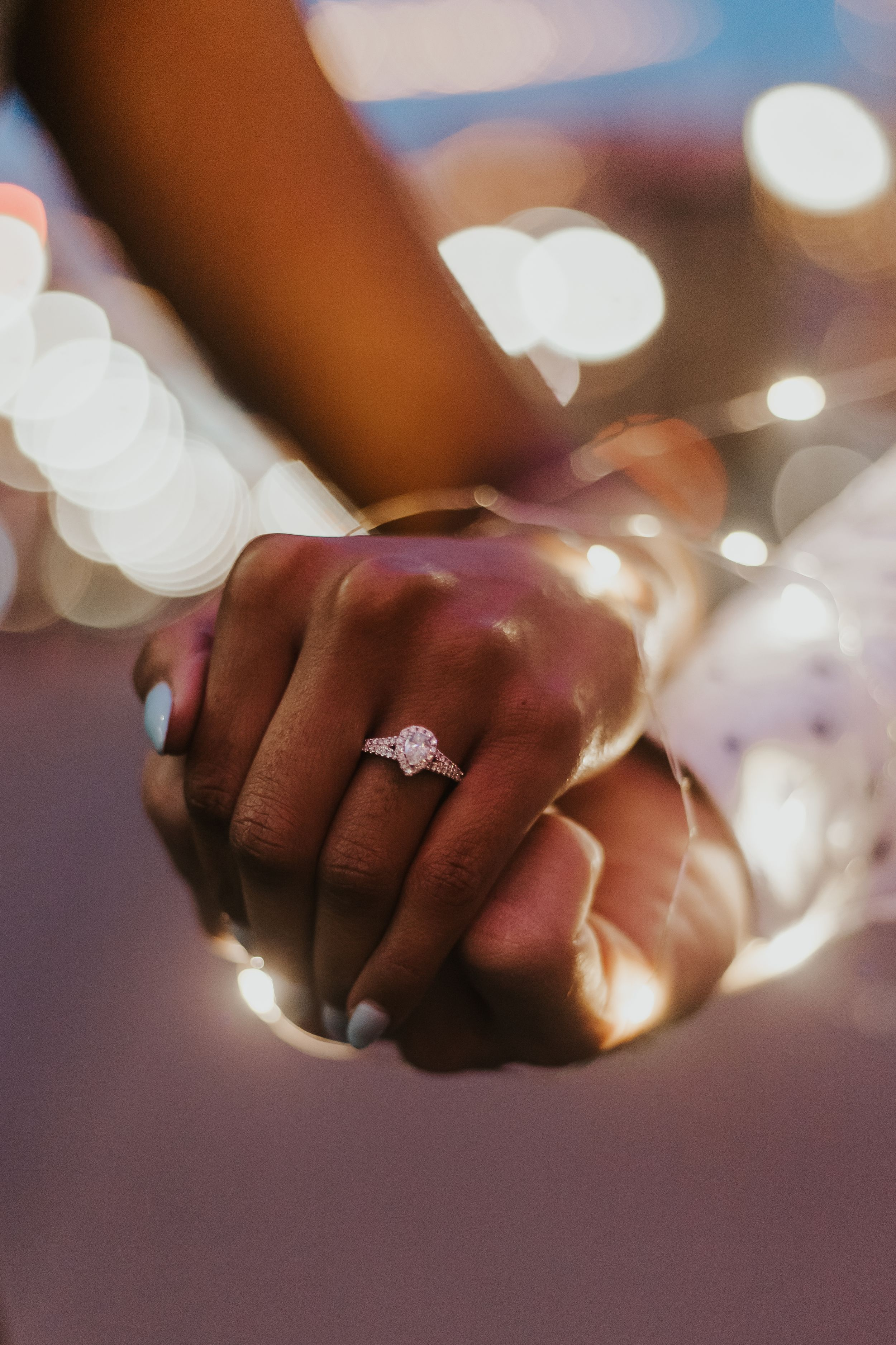 Hands with engagement ring with twinkle lights behind