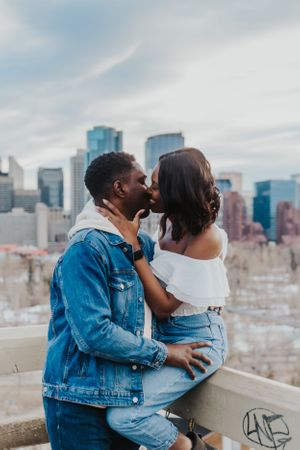 Couple kiss in front of city skyline