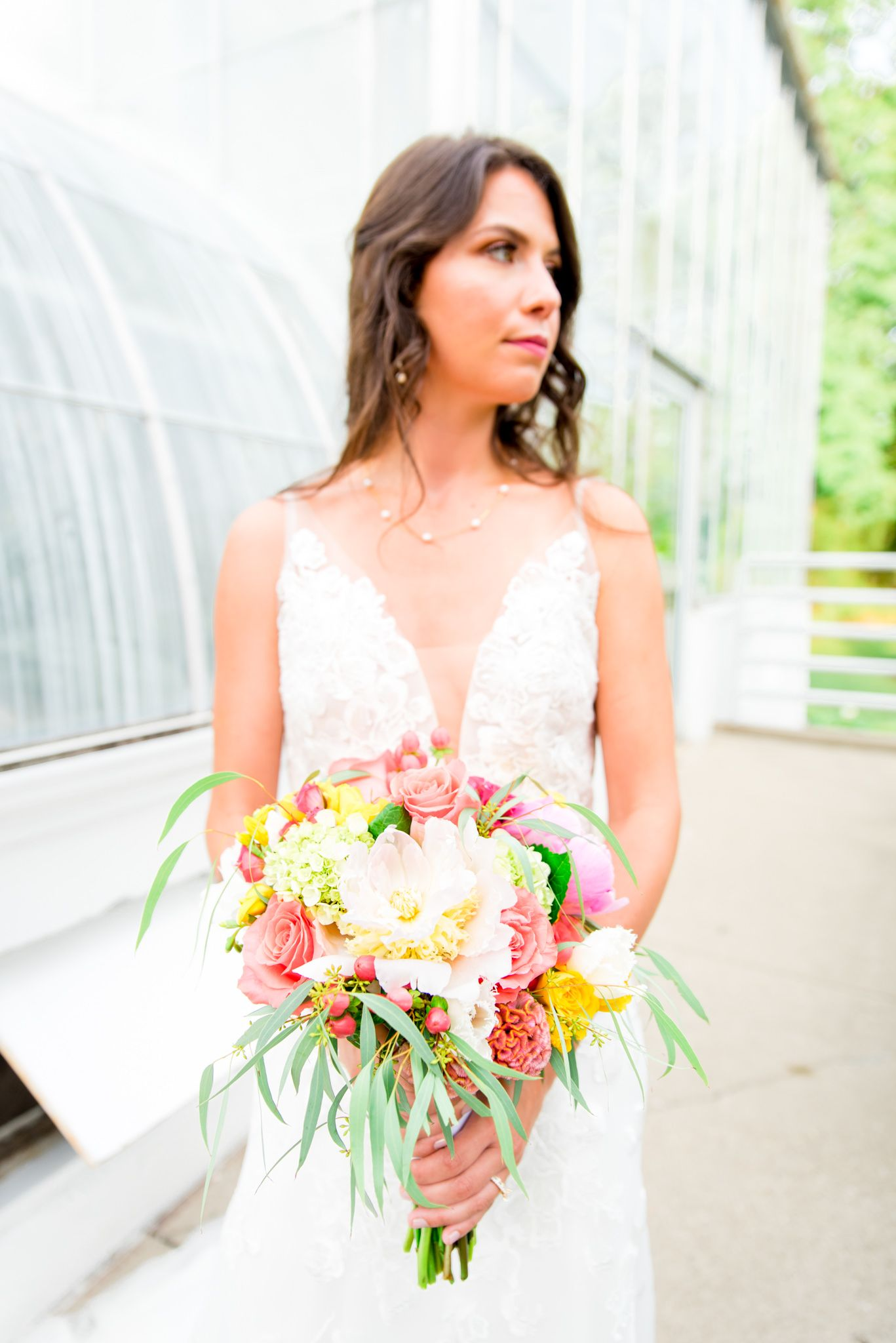 bride holding pink and yellow peony wedding bouquet in front of Krohn Conservatory at summer wedding in Cincinnati