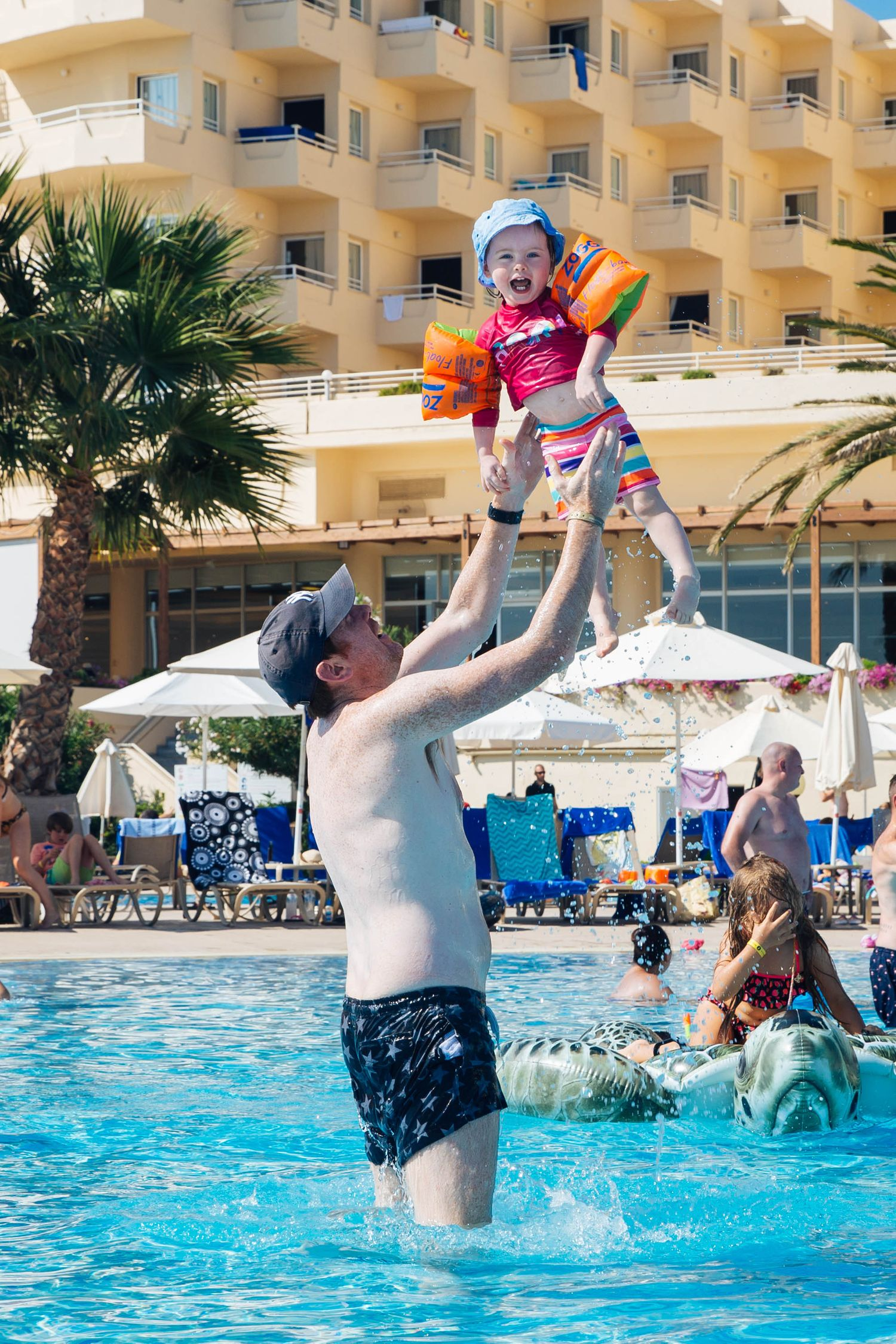 summer holiday in crete greece dad throwing daughter in the air
