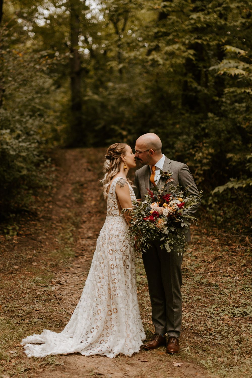 Bride and groom go in for a kiss in the woods at a Minneapolis park. Lindsay Miller Photography