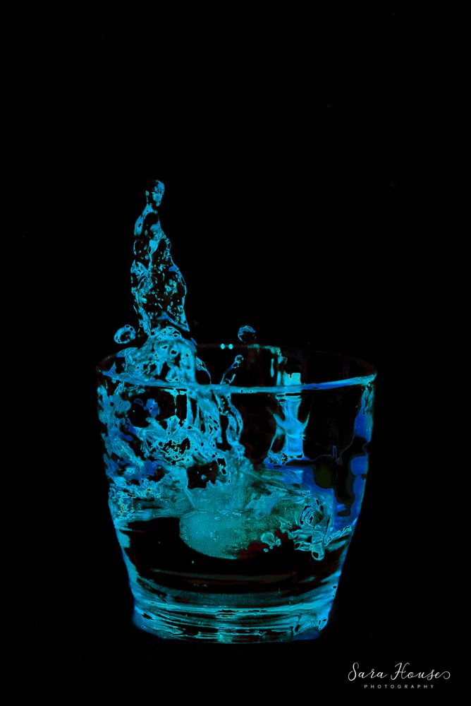 Water splash photo of grape being dropped into a glass of blue water