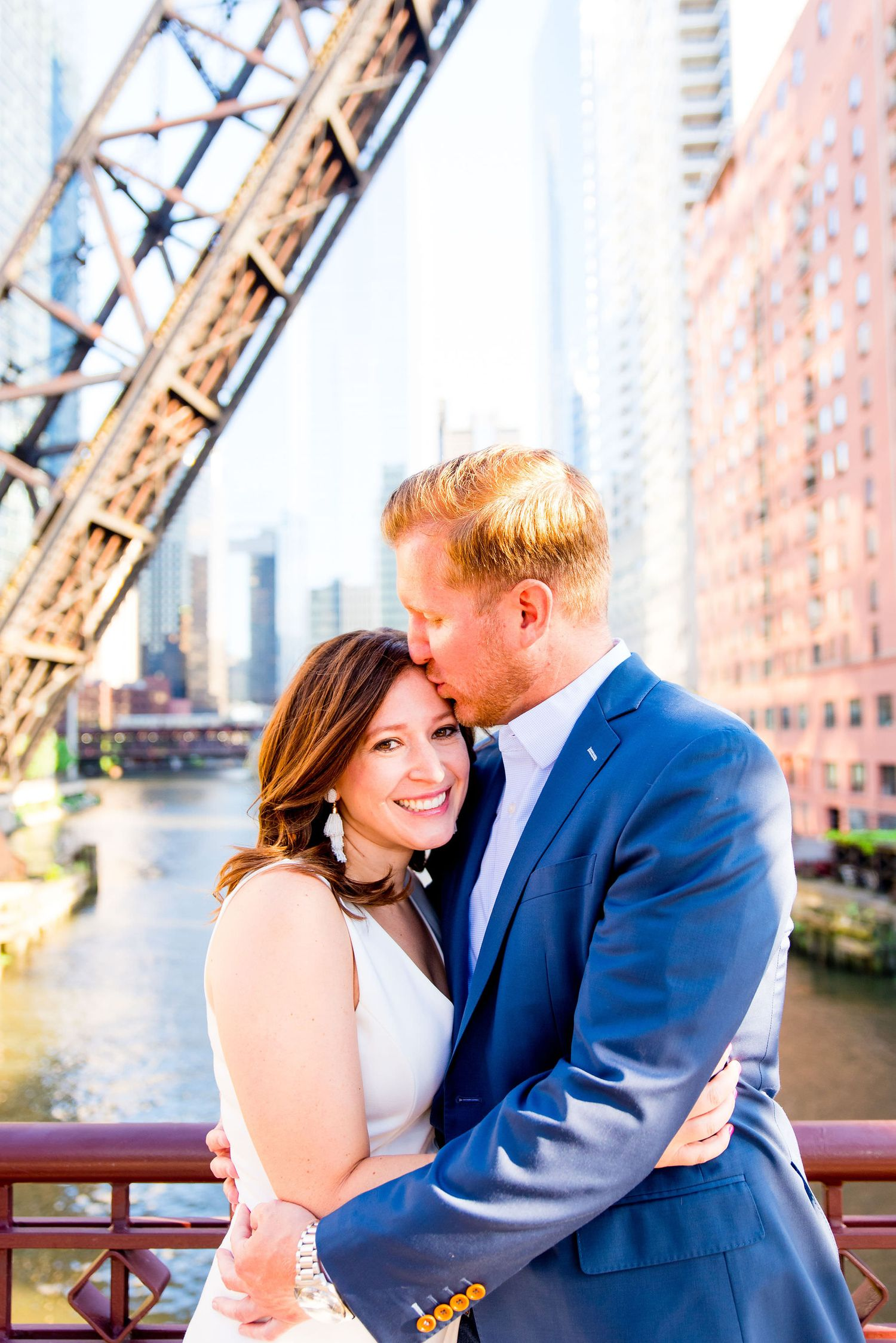 man in navy suit and woman in white dress hugging in front of Chicago River for sunset engagement pictures in Chicago
