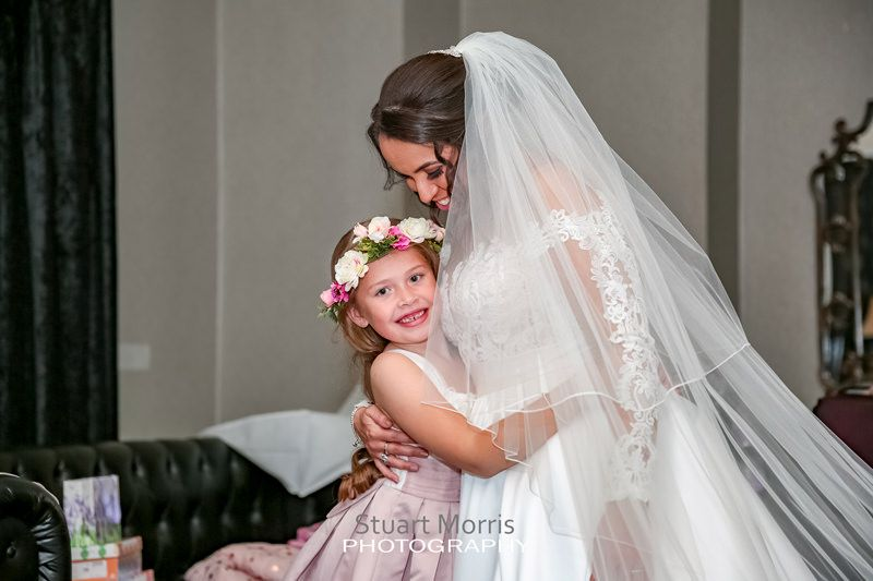 bride gets a hug from the young flower girl