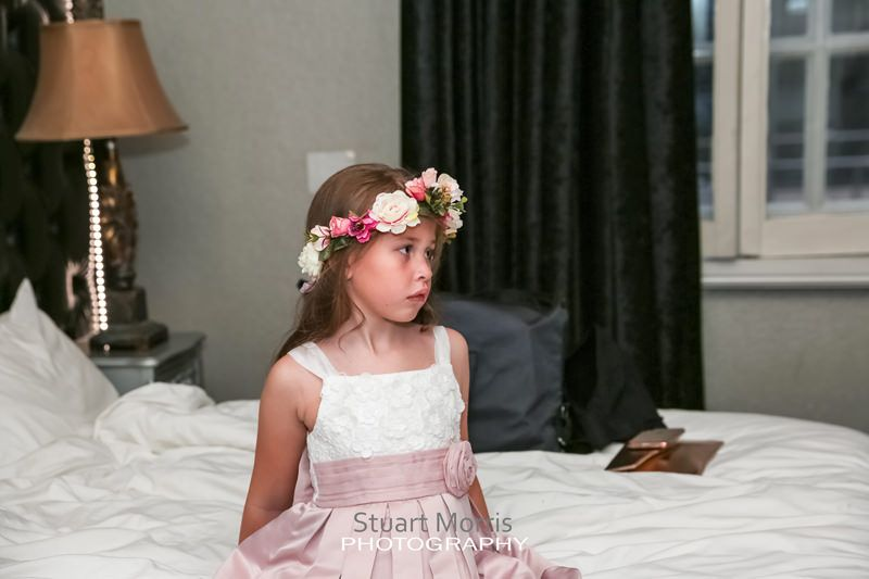 young flower girl sitting on the bed during the bridal prep at 30 james street