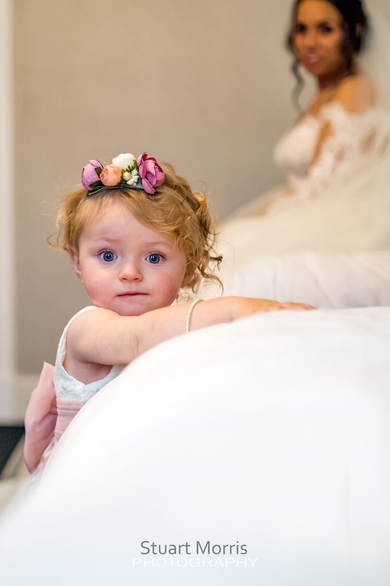 little flower girl looks straight at the camera while leaning on the bed bride sits on the bed in the background