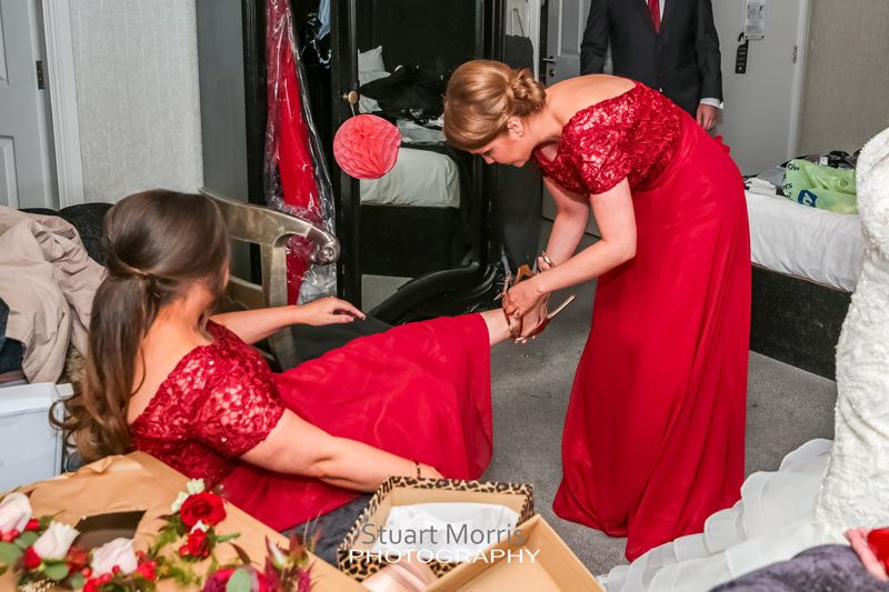 bridesmaid helping another bridesmaid put her shoe on