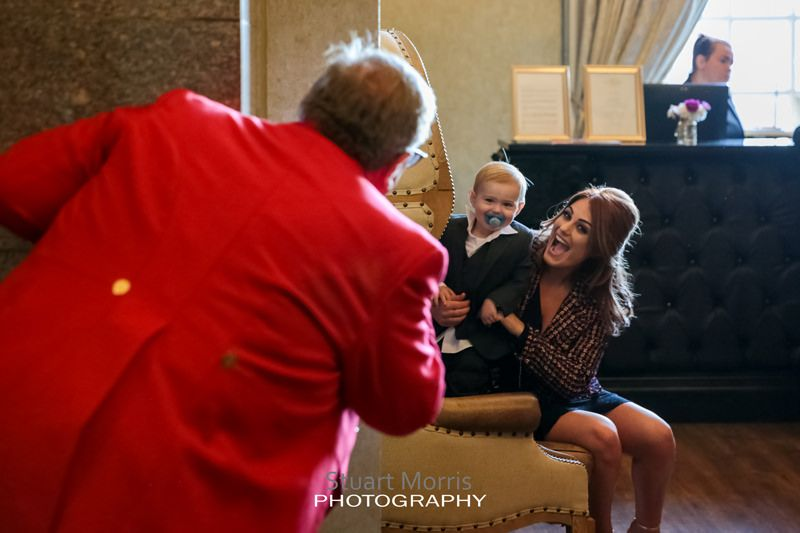 wedding toastmaster plays peekaboo with a young boy sitting on his mums knee at 30 james street