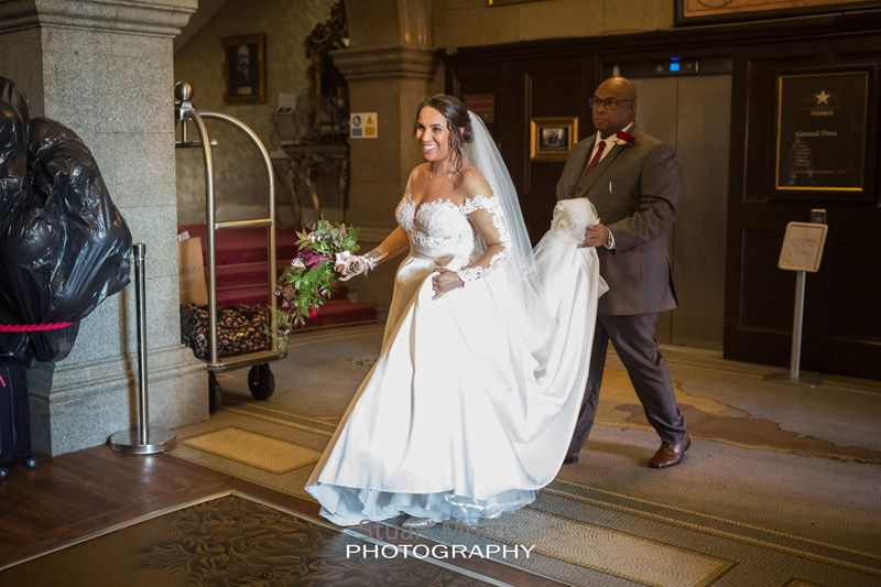 bride walks through the lobby at 30 james street he dad carrying the back of her dress