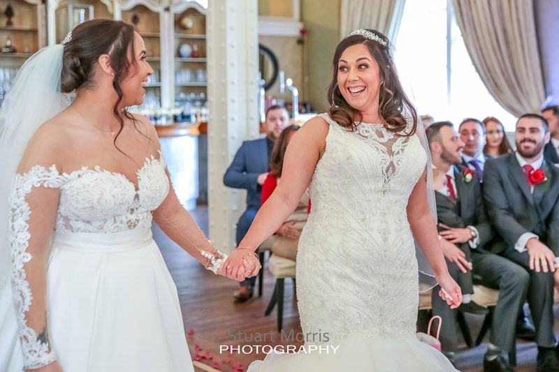 brides turn to look at each other smiling during the ceremony