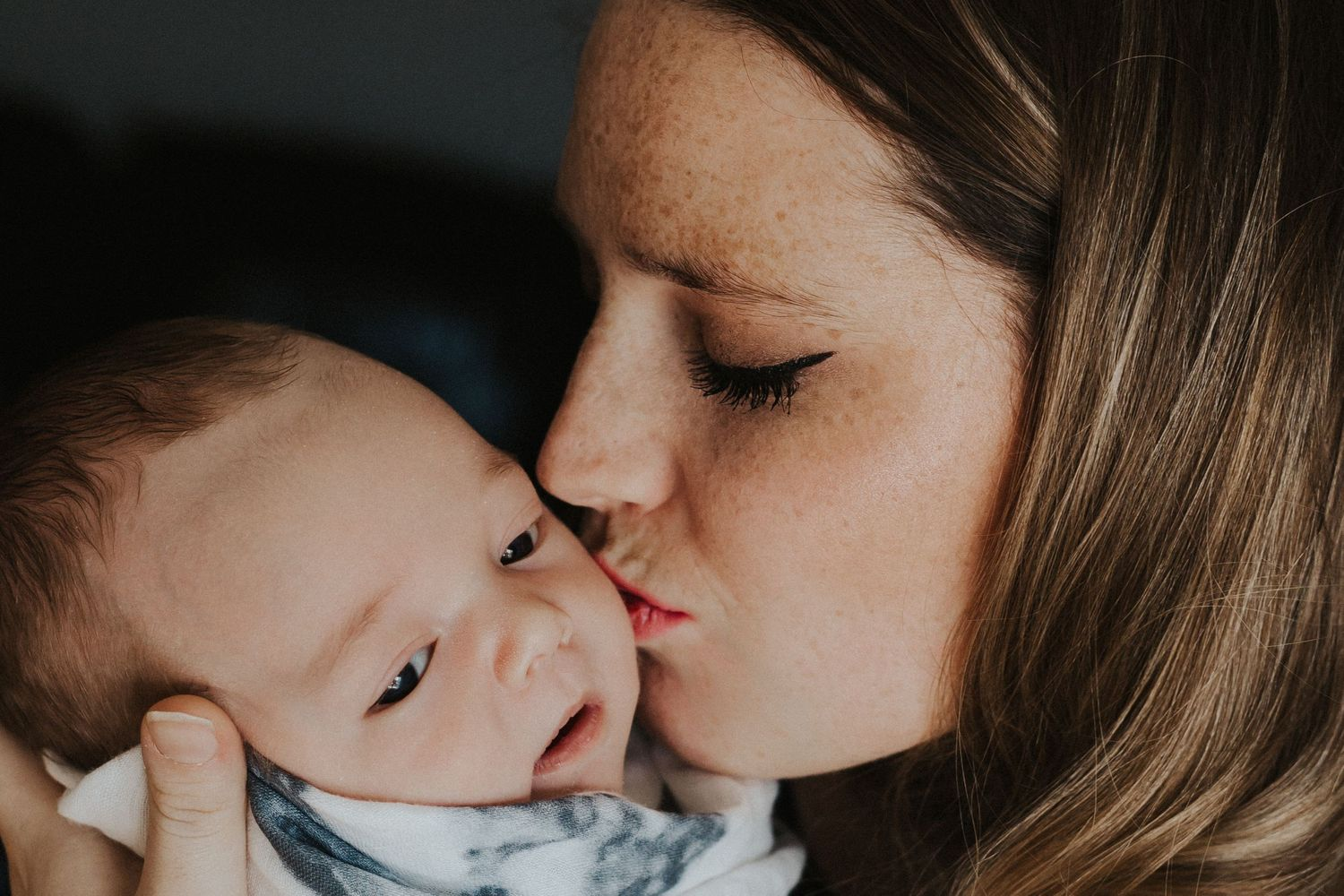 mother kisses baby boy on the cheek while holding him in her arms