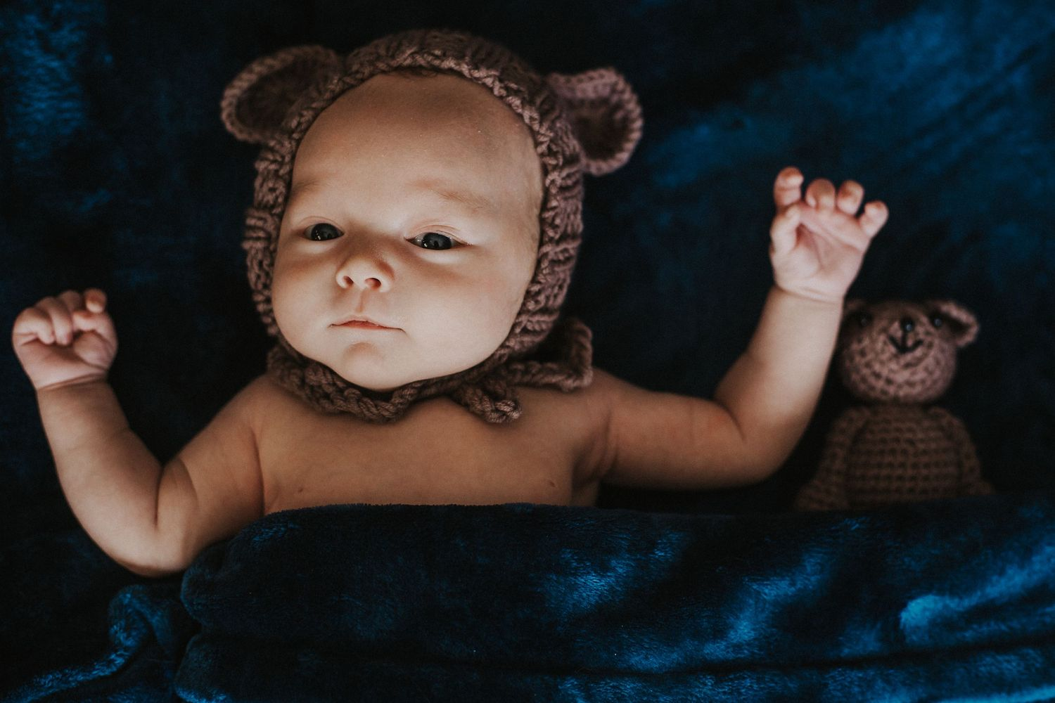 baby boy in bear hat looks up with arms raised up beside his head
