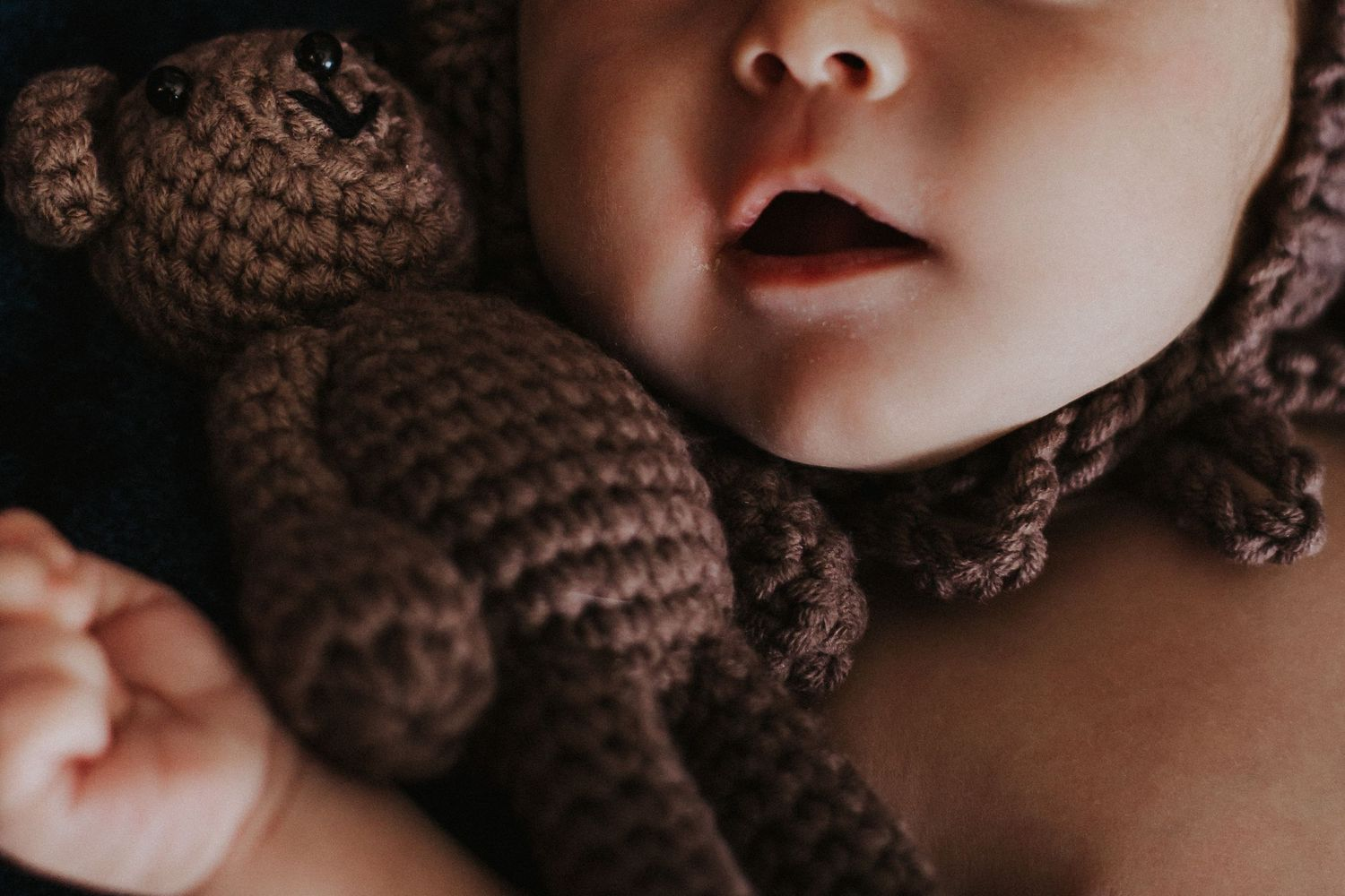 baby boy cuddles close to toy bear