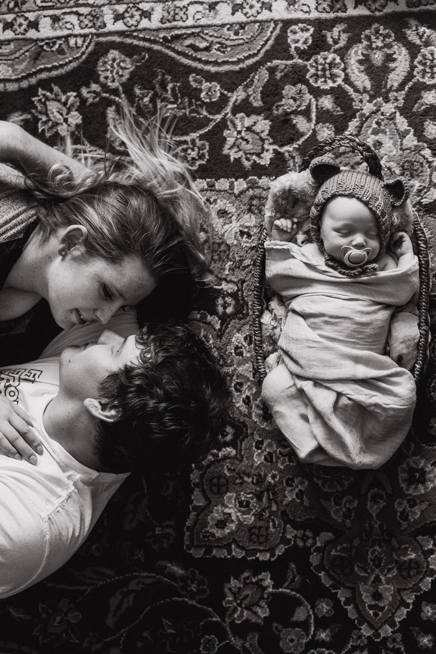parents look at each other while laying on the floor with newborn baby beside them in a basket
