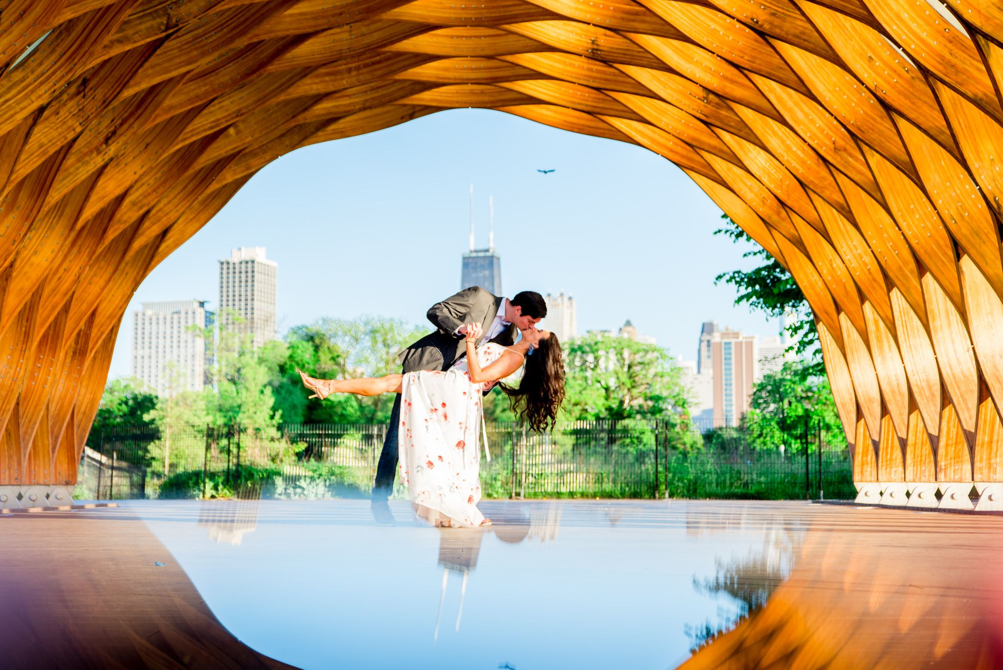 man in suit dipping and kissing woman under Honeycomb at Lincoln Park for engagement pictures in Chicago at sunset