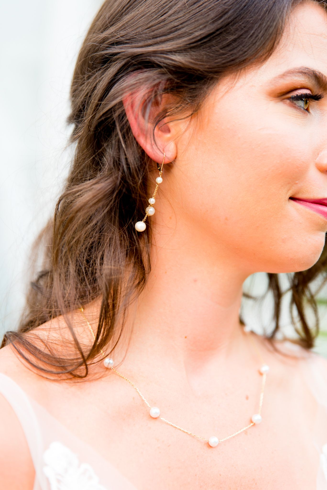 profile of brown haired bride wearing gold peal dangle earrings and gold pearl necklace for wedding