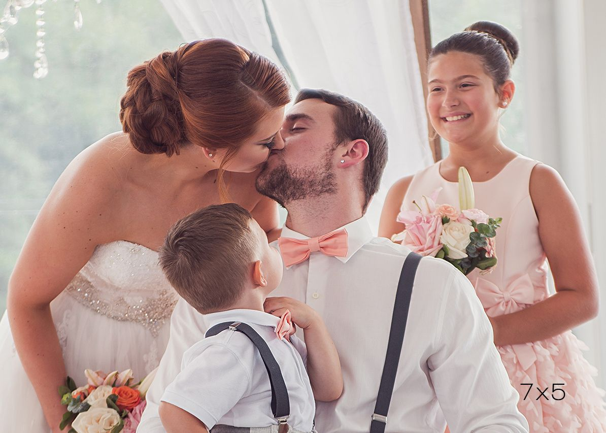 7x5 crop of bride and groom kissing while children look on