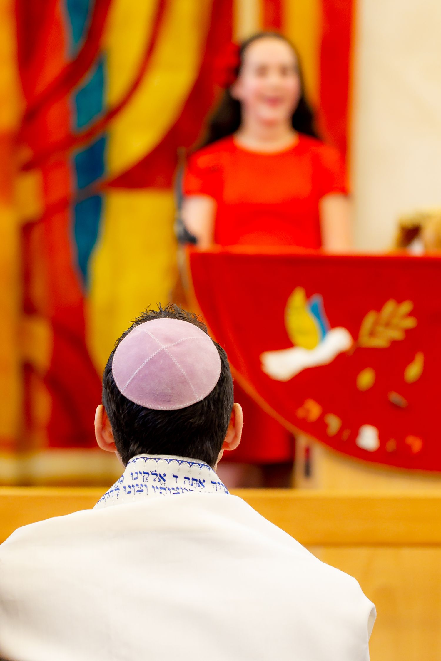 The rear view of a father watching his daughter during her Bat Mitzvah rehearsal - Bat Mitzvah photography