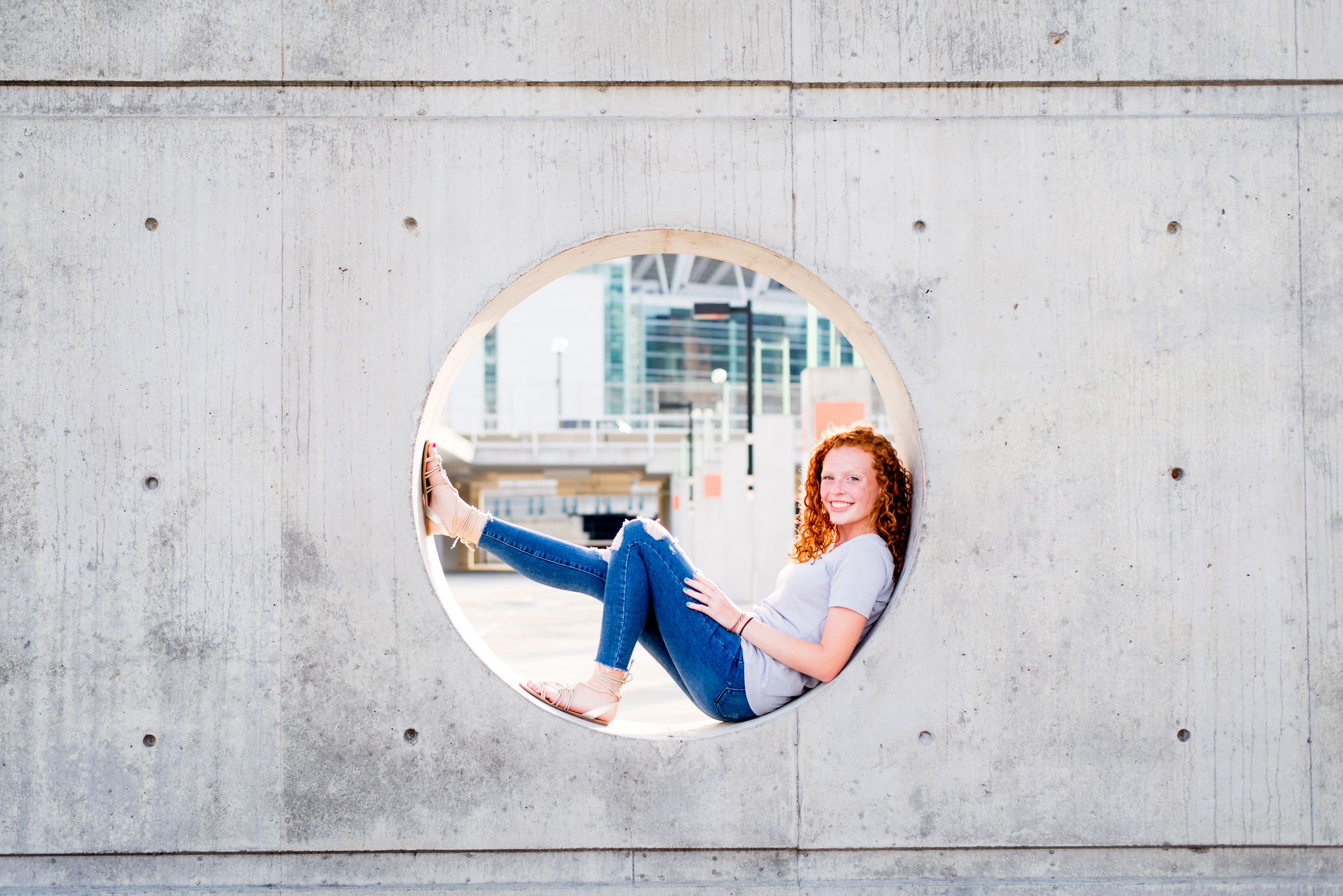 young woman with red curly hair sitting inside a circle cut out of concrete in a Cincinnati parking garage