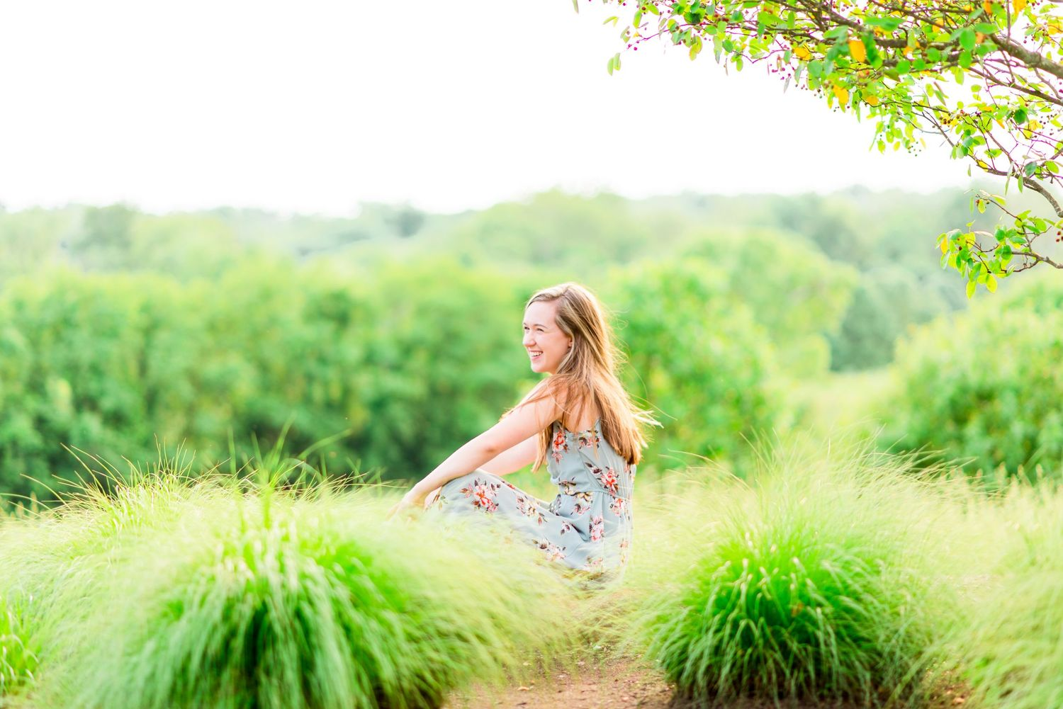 young woman sitting in field of tall light green grass under overcasts sky laughing for Chicago senior pictures
